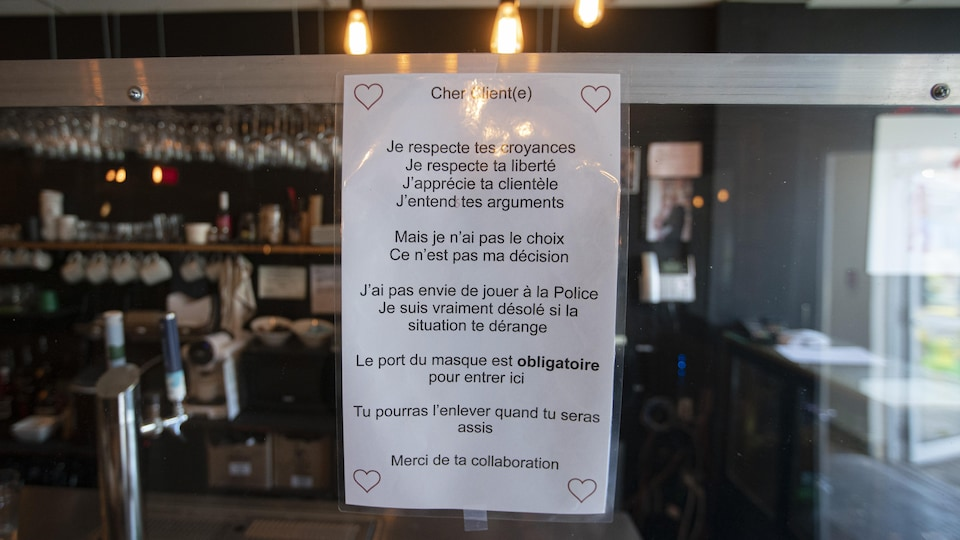 Une petite affiche fixée sur la porte d'un restaurant explique aux clients la nécessité de porter un couvre-visage pour entrer dans cet établissement.