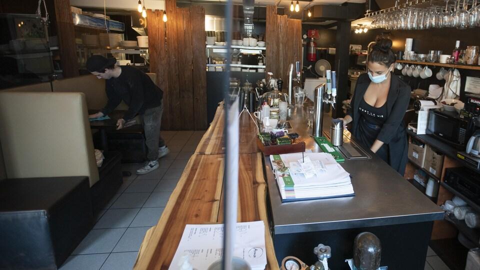 Deux employés sont à l'oeuvre dans un petit restaurant.