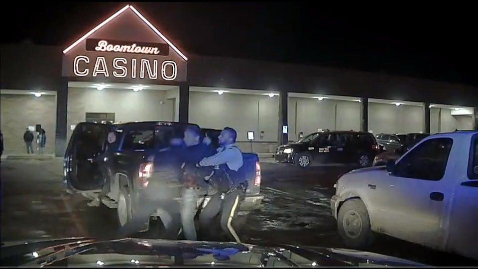 Deux policiers interviennent pour arrêter une personne.
