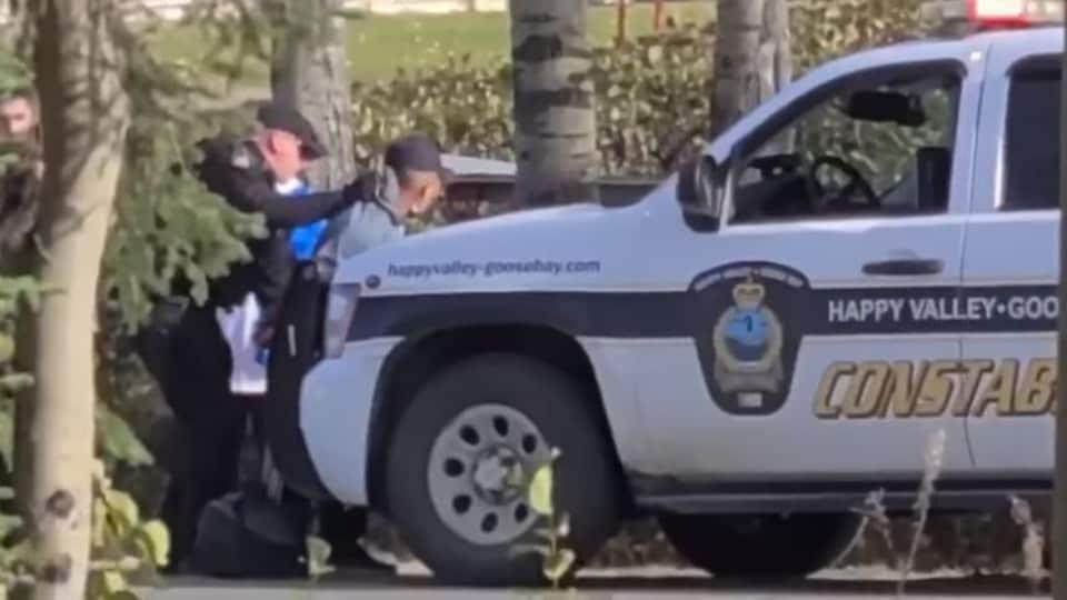 Un agent municipal arrête un homme et le tient devant sa voiture.