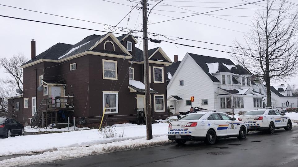 Deux véhicules de la GRC devant une maison dans un quartier résidentiel.