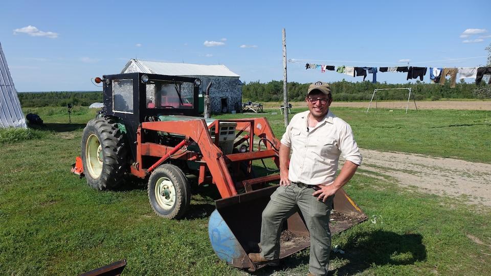Kevin Arseneau, député vert à la législature du Nouveau-Brunswick, posant devant son tracteur. Il a fondé une coopérative agricole.