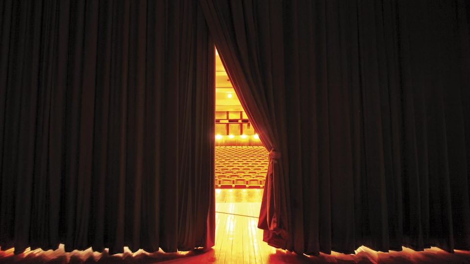 Un rideau de théâtre rouge, entrouvert montre la salle éclairée et des sièges vides.