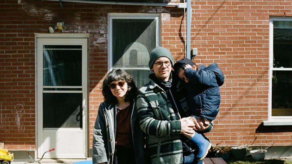 Un couple et un enfant posent devant leur maison.