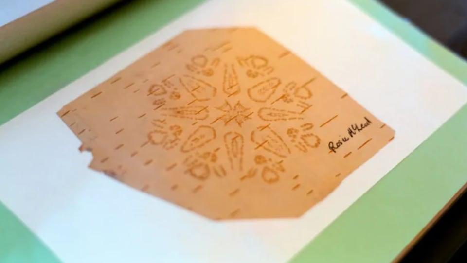Un morceau d'écorce de bouleau où des motifs et formes géométriques peuvent être vus.