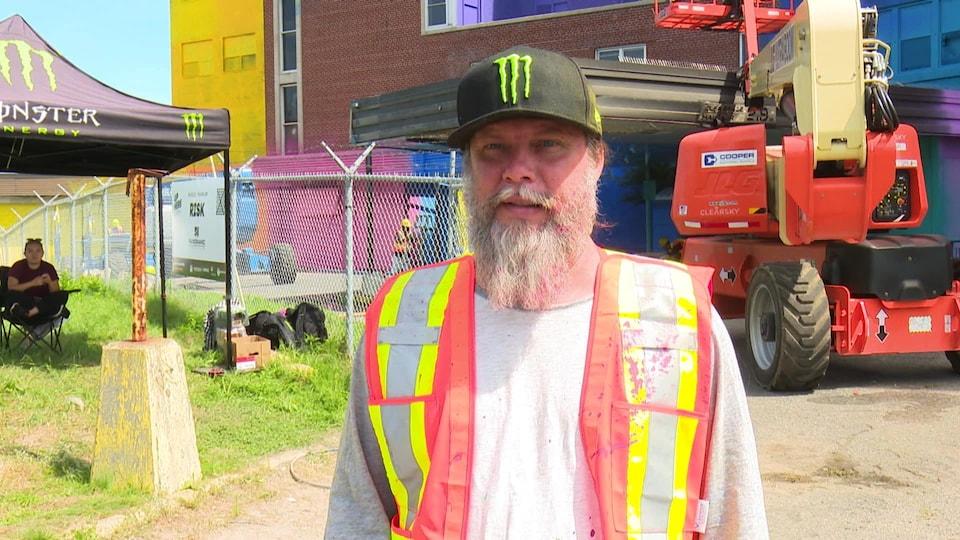 Un homme avec une grosse barbe qui porte une veste fluorescente et un casquette noire