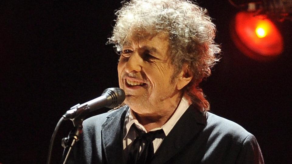Bob Dylan, au micro, sourit.