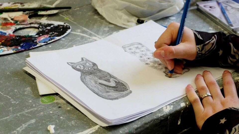 Une étudiante qui dessine un chat.