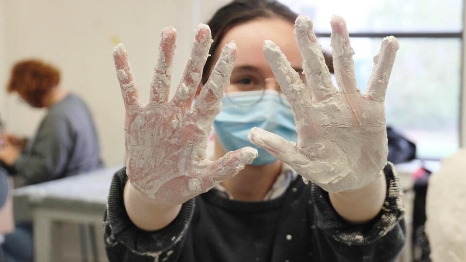 Léanne présente ses mains pleines de plâtre.