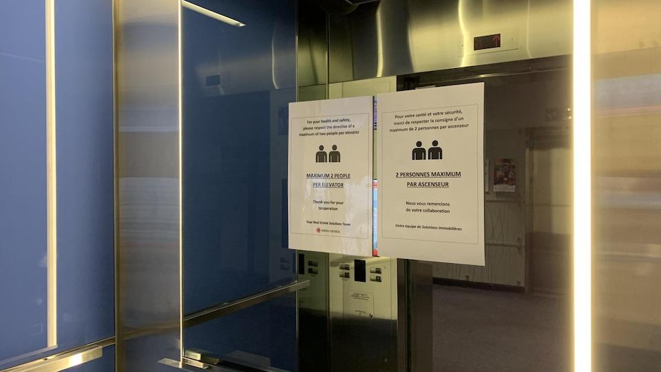 L'intérieur d'un ascenseur, avec une affiche qui indique qu'un maximum de deux personnes peuvent occuper l'espace à la fois.