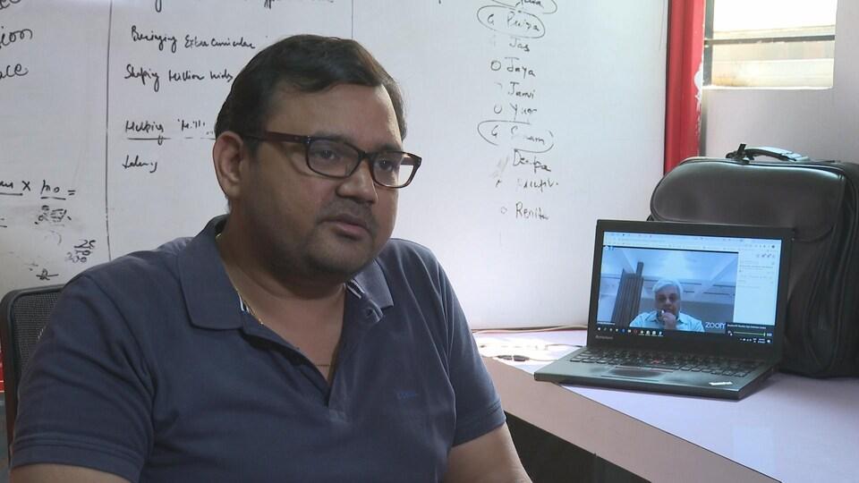 Un homme portant des lunettes assis dans un bureau avec un ordinateur allumé.