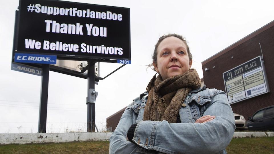 Ashley MacDonald pose devant un panneau sur lequel est écrit : #supportforjanedoe thank you we believe survivors.