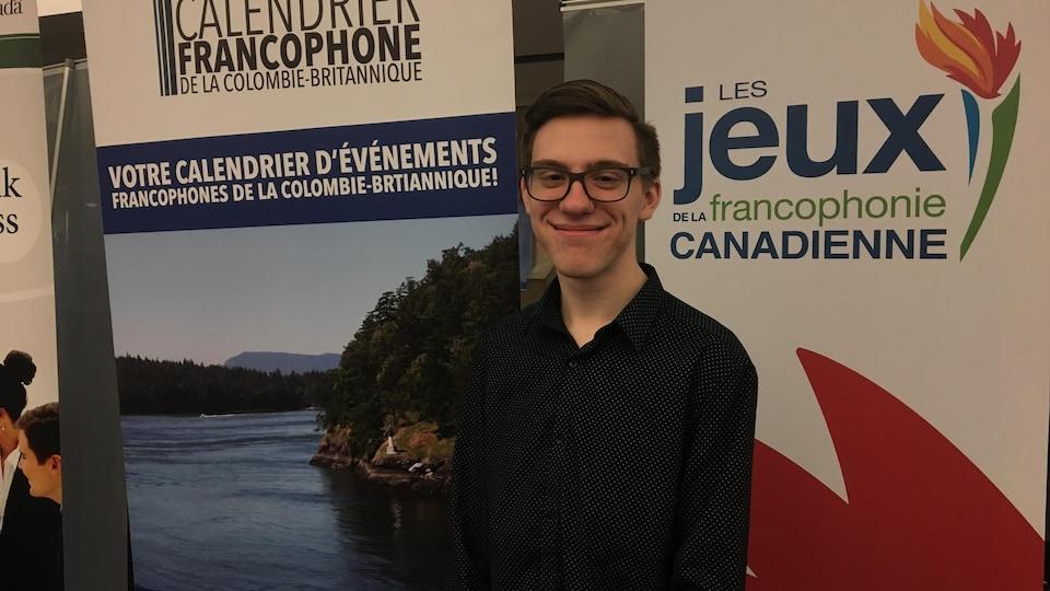 Ashton Ramsay aux journées de la francophonie à Vancouver. Il est debout devant son kiosque d'information. Il sourit.