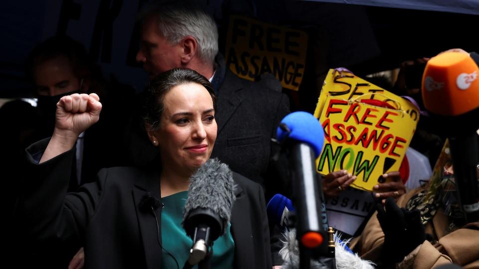 Une femme lève le poing devant les micros des médias.