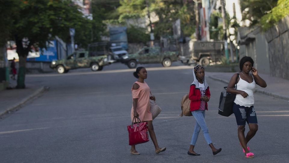 Trois femmes marchent dans une rue. Des véhicules militaires sont visibles en arrière-plan.