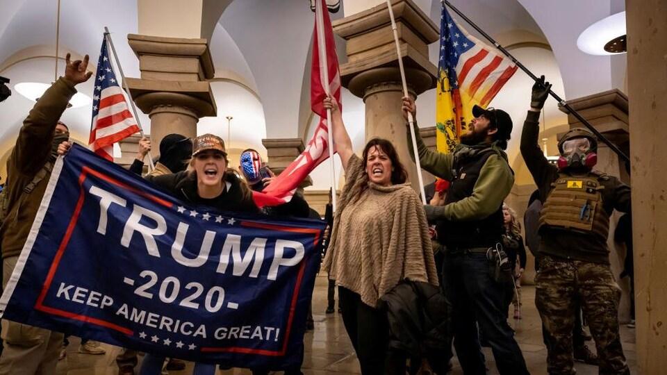 Des manifestants tiennent des drapeaux, notamment des États-Unis et à l'effigie de Trump