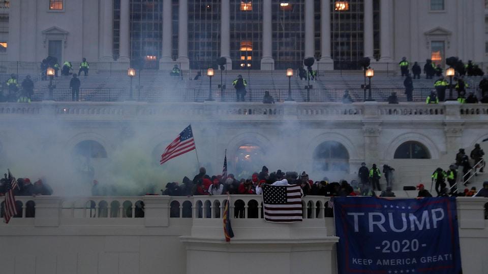Des manifestants envahissent le Capitole malgré la fumée de gaz lacrymogènes.