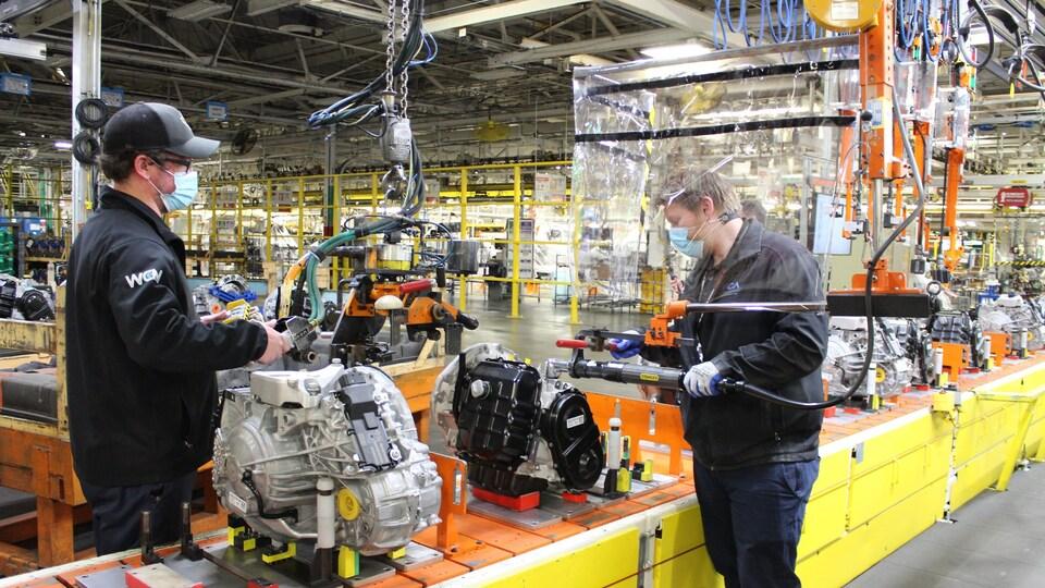 Des employés de Fiat Chrysler portant des masques travaillent sur une chaîne de montage.