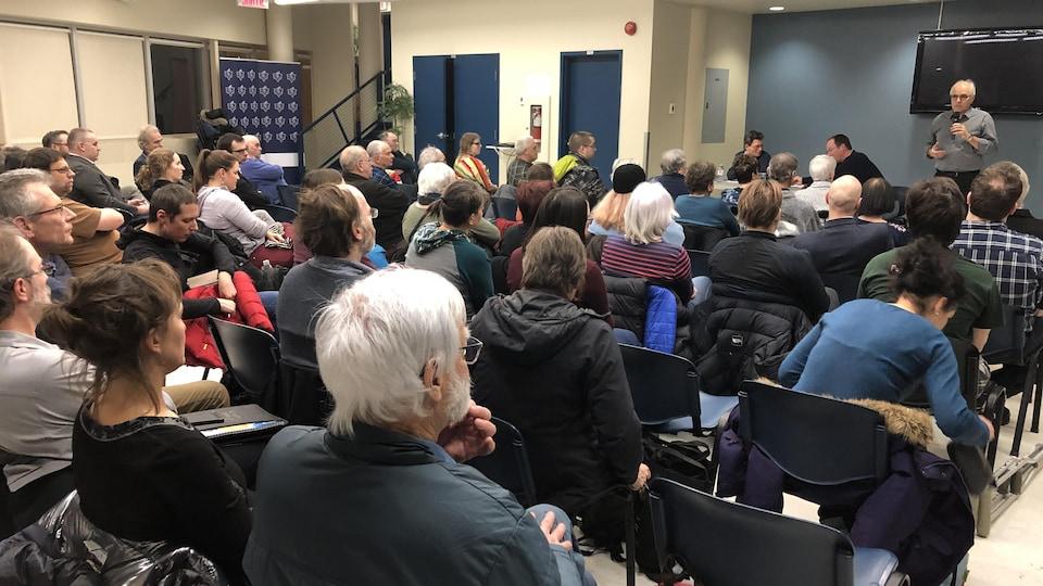 Des citoyens assis en rangées dans une salle écoutent Marc Saint-Laurent.