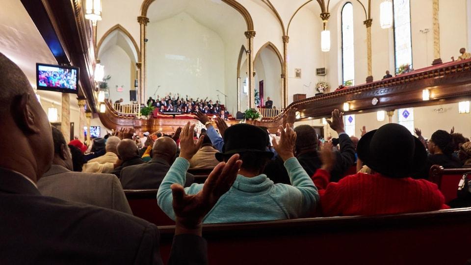 On voit, de dos, des fidèles assis, réunis en prière dans l'église baptiste d'expression française de Brooklyn.