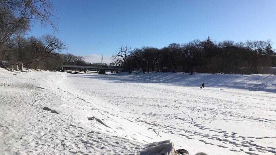 Une rivière vue de sa rive, alors que tout est recouvert de neige.