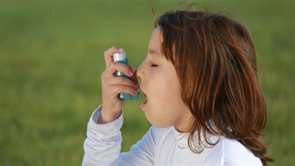 Une fillette asthmatique qui prend son inhalateur.
