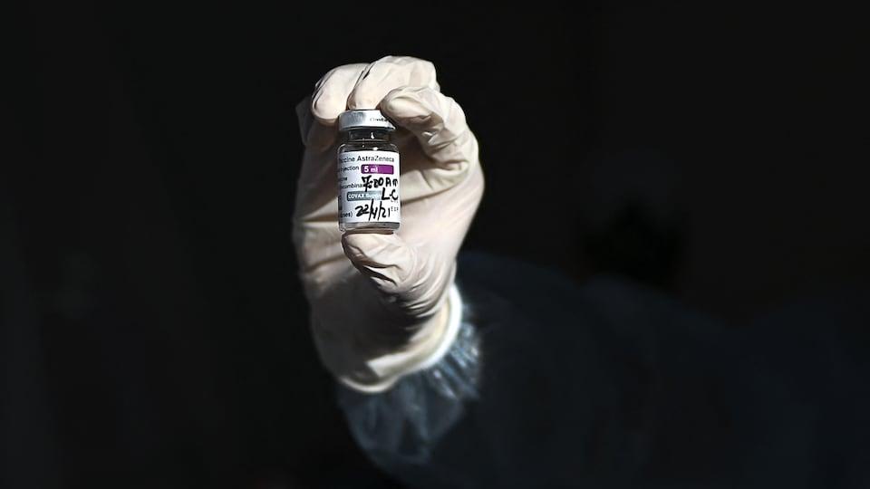Une main gantée tient une fiole du précieux vaccin.