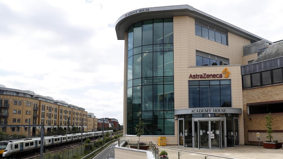 Un immeuble moderne avec le logo d'AstraZeneca en façade, près d'une voie où circule un train dans un quartier résidentiel.