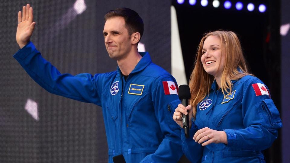 Joshua Kutryk et Jenni Sidey, vêtus de la combinaison bleue de l'Agence spatiale canadienne saluent la foule.