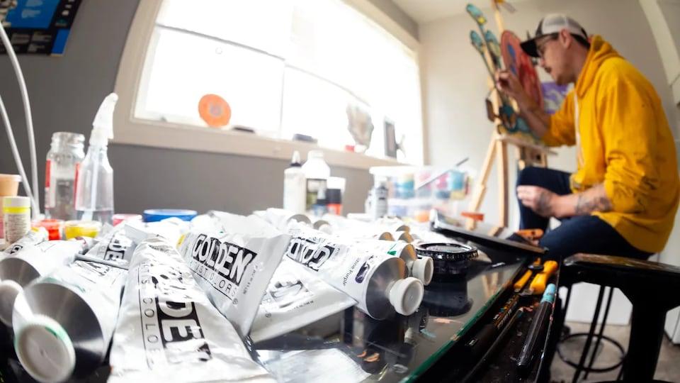 L'artiste Darian Woroniak assis devant une oeuvre en cours de réalisation dans son atelier avec des tubes de peinture posés à côté de lui.