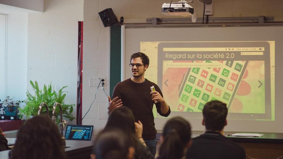 Charles-Antoine est devant un écran où est projetée une présentation destinée aux élèves, qui sont assis à leurs pupitres.