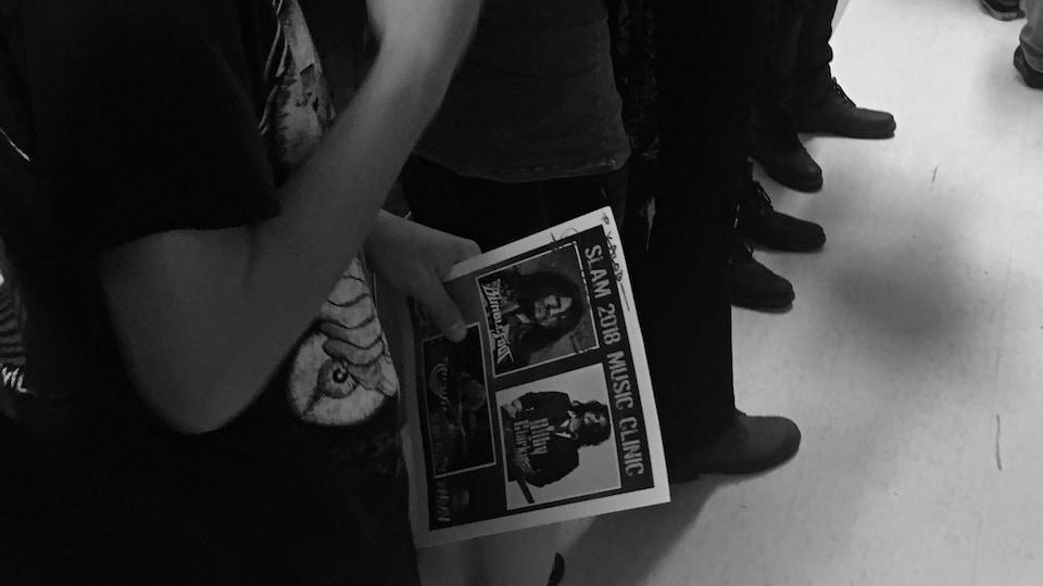 Une file d'attente où l'on peut apercevoir des gens tenant des affiches dans leurs mains pour se la faire dédicacer.
