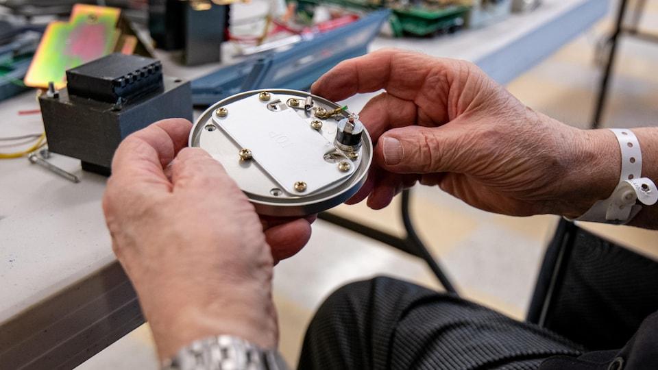 Un homme démonte une pièce de métal remplie de vis.