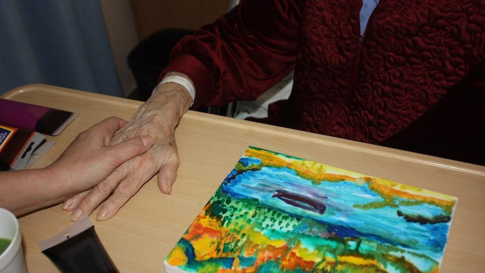Une dame âgée et son oeuvre, une toile colorée.