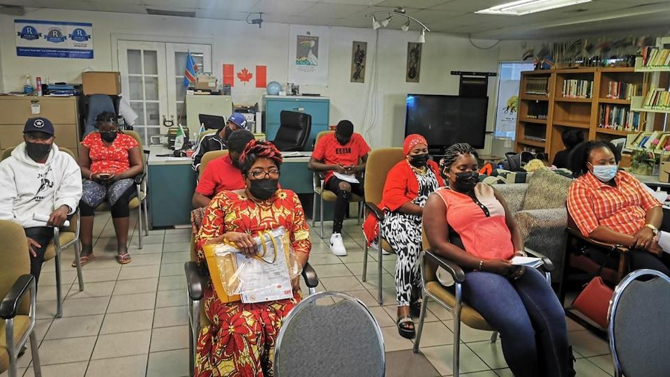 Des adultes portant un masque sont assis sur des chaises dans une salle de classe.