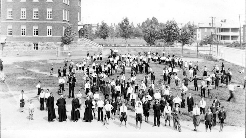 photo ancienne de personnes dans la cour devant le bâtiment