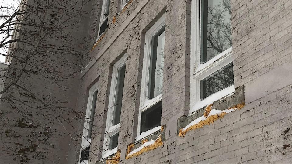 Les bordures de fenêtres des Ateliers Saint-Louis tombent en ruines.
