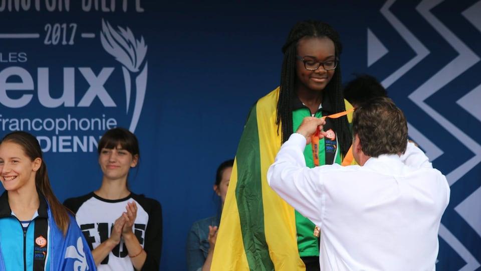 Malika Yoh, 15 ans, reçoit une de ses 4 médailles de bronze en athlétisme aux Jeux de la francophonie canadienne à Moncton-Dieppe.