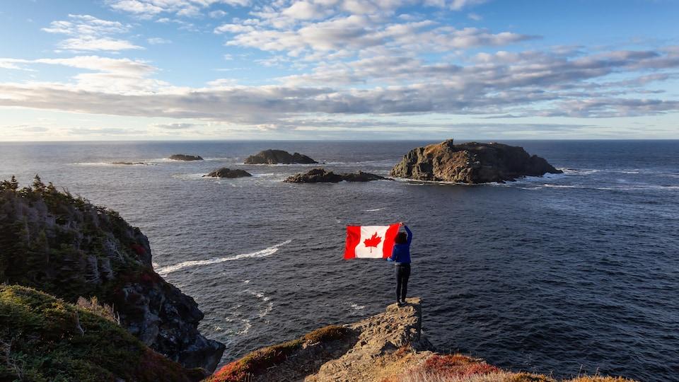 Une femme sur un rocher agite un drapeau du Canada face à l'océan Atlantique, à Sleepy Cove, Terre-Neuve-et-Labrador.