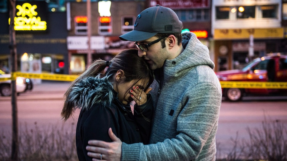 Un homme tient sa femme dans les bras près des lieux de l'attaque.