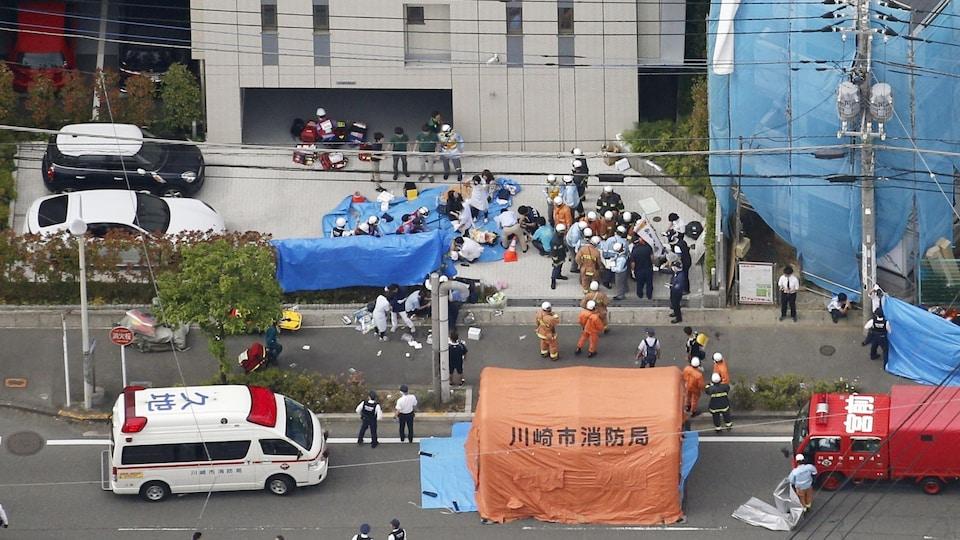 Photo aérienne montrant la scène de l'attaque perpétrée à Kawasaki; on y voit notamment, de loin, des victimes étendues sur une couverture bleue et des véhicules d'urgence.
