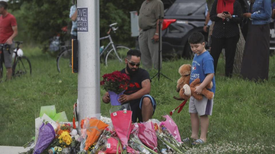 Un homme et un garçon déposent des fleurs et des peluches autour d'un feu de circulation.