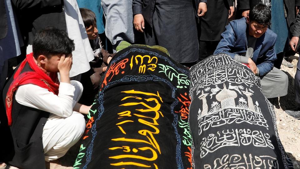 Deux cercueils et des personnes agenouillées, endeuillées.