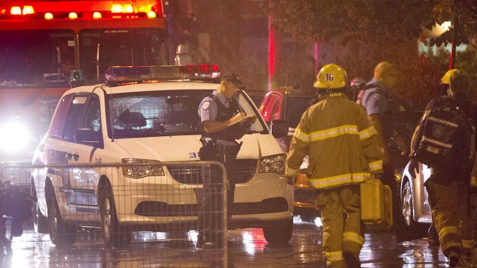 Des policiers et des pompiers sous la pluie.