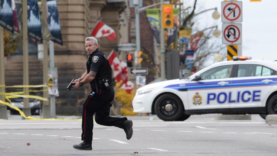 Un policier d'Ottawa court près du Parlement, arme au poing, le 22 octobre 2014.
