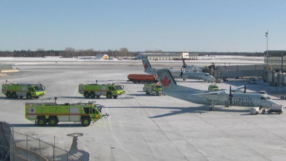Un avion sur le tarmac de l'aéroport d'Ottawa, entouré de véhicules de secours.
