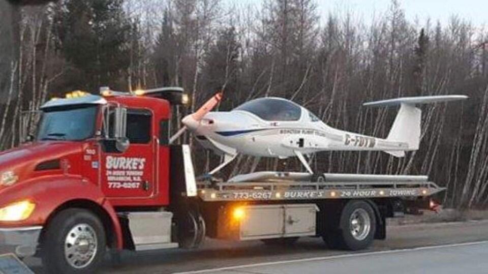Un camion de remorquage sur lequel est posé un petit avion.