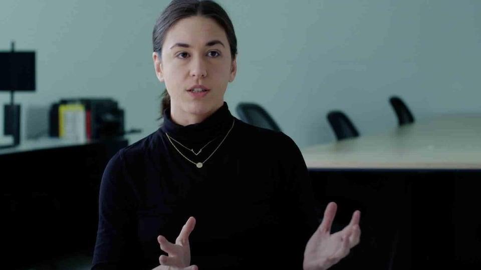 La jeune femme parle en ouvrant les mains.