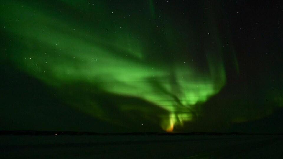 Une aurore s'étend dans le ciel étoilé avec des teintes de vert et de rouge.