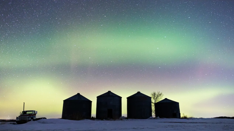 Quatre petits bâtiments sous un ciel qui montre des aurores boréales.